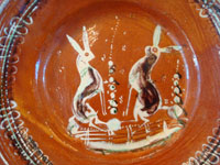 Mexican vintage pottery and ceramics, a beautiful bandera-ware plate or bowl, with wonderful artwork featuring two lovely bunnies, Tonala or Tlaquepaque, Jalisco, c. 1930's. Closeup photo of the bunnies on the front of the bandera-ware plate or bowl.
