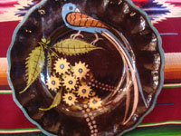 Mexican vintage pottery and ceramics, a lovely black-ware plate with a beautiful bird (a quetzal?) and fantastic flowers, Tlaquepaque or Tonala, Jalisco, c. 1920-30's.  Closeup photo of the bird and flowers on the front of the Tlaquepaque vintage pottery plate.