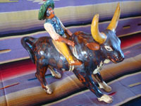 Mexican vintage folk art, and Mexican vintage pottery and ceramics, a wonderful pottery piece depicting a bull-rider confidently riding a fierce and raging bull, Michoacan, c. 1930's. Main photo of the pottery figure from Michoacan.