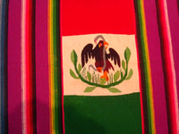 Mexican vintage textiles and sarapes, a textile or sarape woven of fine wool and representing the Mexican flag and national symbol of the eagle with snake, c. 1940. The piece bears the traditional colors of the Mexican flag: red, green, and white. Closeup photo of the eagle on the front of the sarape.