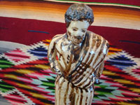 Mexican vintage folk-art, and Mexican vintage pottery and ceramics, a wonderful pottery statue of a Mexican caballero with a sarape gracefully draped over his shoulder and wearing a wonderful striped suit, attributed to the great folk-artist, Senora Pena of Tzintzuntzan, Michoacan, c. 1960's. Closeup photo of the caballero's face.