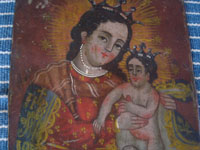 Mexican vintage devotional art, and Mexican vintage tinwork art, a very beautiful retablo painted on tin and depicting Nuestra Senora del Refugio (Our Lady Refuge of Sinners), c. early to mid-20th century. Closeup photo of the faces of the retablo.