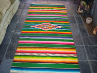 Mexican vintage textiles and sarapes, a beautiful Saltillo sarape with a green background, c. 1940's. Very fine wool with silk in the center medallion and decorative side bars. Main photo.