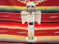 Native American Indian antique folk art, a carved, bone totem pole from Alaska, c. 1920-30's. The figure of the Raven with outstretched wings (the mythical hero of the Tlingit) hovers at the top of the pole, sheltering the three children of the sun. Main photo of the totem pole.