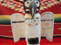 Native American Indian antique folk art, a carved, bone totem pole from Alaska, c. 1920-30's. The figure of the Raven with outstretched wings (the mythical hero of the Tlingit) hovers at the top of the pole, sheltering the three children of the sun. Photo of the Raven at the top of the pole.