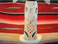 Native American Indian antique folk art, a carved, bone totem pole from Alaska, c. 1920-30's. The figure of the Raven with outstretched wings (the mythical hero of the Tlingit) hovers at the top of the pole, sheltering the three children of the sun. Photo of the bottom third of the pole.