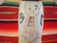 Native American Indian antique folk art, a carved, bone totem pole from Alaska, c. 1920-30's. The figure of the Raven with outstretched wings (the mythical hero of the Tlingit) hovers at the top of the pole, sheltering the three children of the sun. Photo of the center of the pole showing a face.