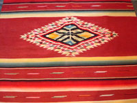 Mexican vintage sarapes and textiles, an incredible Saltillo sarape with a beautiful center medallion, c. 1930's. The predominant color of this multi-colored piece is a beautiful red. Photo showing the center medallion of the Saltillo sarape.