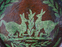 Mexican vintage pottery and ceramics, a beautiful pottery charger with wonderful decorations and glazing, Oaxaca, c. 1950's. The artwork features two playful llamas surrounded by lovely olive leaves. Closeup photo of the Mexican pottery charger from Oaxaca.