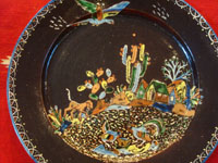 Mexican vintage pottery and ceramics, a beautiful blackware pottery plate with wonderful decoration featuring a dog, chicken, rooster, and parrot at the scenic rancho and amidst lovely cacti and other plants, Tlaquepaque, Jalisco, c. 1930's. Closeup photo of the front of the plate.