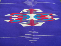 Vintage New Mexican textiles, a lovely woolen textile from the weaving center of Chimayo, New Mexico, c. 1930's. The weaving has a beautiful and very rare purple background, with colorful Chimayo-style design elements in various wonderful colors. Closeup photo of the central medallion.