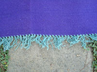 Vintage New Mexican textiles, a lovely woolen textile from the weaving center of Chimayo, New Mexico, c. 1930's. The weaving has a beautiful and very rare purple background, with colorful Chimayo-style design elements in various wonderful colors. Closeup photo of the fringe at one end.