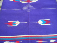 Vintage New Mexican textiles, a lovely woolen textile from the weaving center of Chimayo, New Mexico, c. 1930's. The weaving has a beautiful and very rare purple background, with colorful Chimayo-style design elements in various wonderful colors. Closeup photo of one of the design elemts, resembling an arrow.