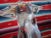 Mexican vintage folk art, and Mexican vintage pottery and ceramics, a wonderful pottery figure of a powerful bull with one happy rider, Guerrero, c. 1940's. Photo focusing on the bull's face.