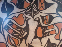 Native American Indian pottery and ceramics, a medium/large dough bowl from Santo Domingo Pueblo, c. 1970-80. The designs painted on the bowl are very beautiful and feature wonderful birds and foliage. Closeup photo of the birds on the front of the bowl.