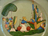 Closeup photo showing the hand-painted village scene on the Talquepaque pottery plate from Jalisco, Mexico.