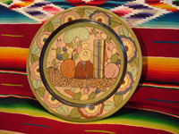 Mexican vintage pottery and ceramics, a petatillo plate from Tlaquepaque, c. 1920-30. This piece is wonderfully hand-painted with a scene of a man sitting in front of a cactus and other colorful plants. Main photo of plate.