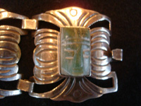 Mexican vintage sterling silver jewelry, and Taxco vintage silver jewelry, a very elegant bracelet with faces of Aztec gods carved of beautiful jade, Taxco, c. 1930's. Closeup photo of one of the faces of an Aztec god formed of green jade.