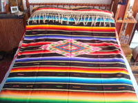 Mexican vintage textiles, and Mexican vintage Saltillo sarapes (serapes), a beautiful, large Saltillo-style sarape with a wonderful central medallion and beautiful color combinations, c. 1930's. Photo of the sarape covering a full-sized bed.