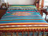 Mexican vintage textiles, and Mexican vintage Saltillo sarapes (serapes), a beautiful Saltillo-style sarape with a lovely turquoise background and a woncerful center medallion and decorative sidebars, c. 1930's. A photo of the sarape covering a bed.