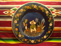Mexican vintage pottery and ceramics, a beautiful pottery charger with a blue background glaze and artwork showing a boy sitting on the ground, Tonala or Tlaquepaque, c. 1930's. Main photo of the charger.