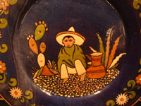 Mexican vintage pottery and ceramics, a beautiful pottery charger with a blue background glaze and artwork showing a boy sitting on the ground, Tonala or Tlaquepaque, c. 1930's. Closeup photo of the boy.