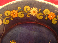 Mexican vintage pottery and ceramics, a beautiful pottery charger with a blue background glaze and artwork showing a boy sitting on the ground, Tonala or Tlaquepaque, c. 1930's. Closeup photo showing the lovely floral border.