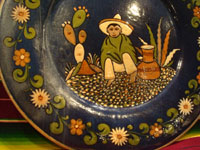 Mexican vintage pottery and ceramics, a beautiful pottery charger with a blue background glaze and artwork showing a boy sitting on the ground, Tonala or Tlaquepaque, c. 1930's. Another photo of the boy on the front of the charger and sitting on the ground.