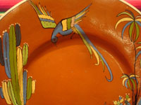 Mexican vintage pottery and ceramics, a beautiful pottery charger with a wonderful glaze in the background and artwork featuring a man going to market with his trusty burros and with a lovely quetzal flying overhead, Tonala or Tlaquepaque, Jalisco, c. 1940's. Closeup photo of the lovely bird at the top of the charger.