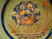 BW-10: Mexican vintage pottery and ceramics, a beautiful Tlaquepaque pottery plate with a graceful and beautiful peacock as the central design element, Tlaquepaque or Tonala, Jalisco, c. 1940's.  Closeup photo of the peacock.