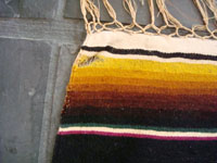 A closeup photo of the vintage Mexican textile, a Saltillo sarape, showing a very small hole.