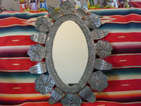 Mexican vintage tin-work, a tin mirror with copper, c. 1950. Size: 25 1/2 inches tall by 15 inches wide. Beautiful floral decorations and wonderful stamping.