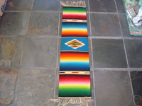 Mexican vintage textile, a Saltillo Sarape, c. 1940. This is a very fine narrow runner, with a rainbow-style of coloration. Very fine wool with a beautiful center diamond.