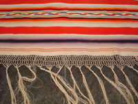 Mexican vintage textiles, and Mexican vintage Saltillo serapes (sarapes), a stunning Saltillo serape with color-hues of soft-red, lilac, purple, green, and soft-yellow, c. 1910-20.  Closeup view of one end of the serape, showing the beautiful fringe.