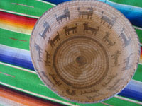 Native American Indian antique woven baskets and basket-weaving, a stunning Pima basket decorated with a figure of a man throwing a stick to his nineteen doggies, Pima, Arizona, c. 1915-20.  Photo shot from above the Pima basket, looking down.