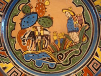 Mexican vintage pottery and ceramics, a beautiful plate with a wonderful Aztec-style border and crisp artwork, attributed to the famous Balbino Lucano, Tonala or Tlaquepaque, c. 1930's. Closeup photo of the scene on the front of the Balbino Lucano Tonala plate.