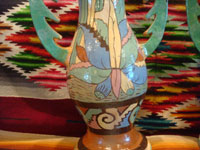 Mexican vintage pottery and ceramics, a pair of very lovely pottery vases with handles and beautiful, hand-painted decorations, Tonala or Tlaquepaque, c. 1940's. Photo of the bottom part of a vase showing a lovely plant and floral decorations.