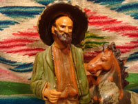Mexican vintage folk art, and Mexican vintage pottery and ceramics, a wonderful pottery figure of a Mexican paisano and his trusty quarter-horse, leaning against a tree stump, originally meant to be an ash tray, Tlaquepaque or Tonala, Jalisco, c. 1930's. Closeup photo of the man's face on the Tlaquepaque pottery piece.