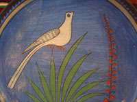Mexican vintage pottery and ceramics, a lovely burnished plate with a beautiful blue background and wonderful artwork, Tonala or Tlaquepaque, Jalisco, c. 1930's. The artwork features a graceful bird and flowers.  Closeup photo of the lovely bird amidst foliage.