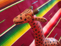 Mexican vintage folk art, and Mexican vintage wood-carvings, a darling woodcarving of a very fanciful and endearing giraffe, Oaxaca, c. 1950's. Closeup photo of the carved wooden giraffe's head.