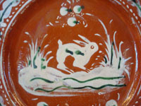 "Mexican vintage pottery and ceramics, a Bandera-ware pottery plate with a wonderful bunny, Tlaquepaque, c.1930. This type of pottery is called bandera (Spanish for ""flag"") because of the colors of red, green, and white, the colors of the Mexican flag. Very fine hand-painted decorations on this piece of vintage Mexican folk art.  Closeup photo."