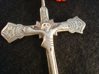 Mexican vintage silver jewelry, a Mexican or Guatemalan silver cross, c. 17th-18th century. This is a colonial era devotional cross showing significant indigenous, pre-hispanic influence. Closeup photo of silver cross.