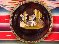 Mexican vintage pottery and ceramics, a blackware plate with wonderful artwork from Tlaquepaque, Jalisco, c. 1930-40's. The plate has a beautiful border and a scene of a campesino carrying his heavy load amidst plants and cacti.  Main photo.