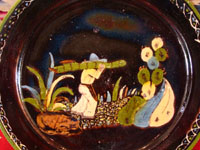 Mexican vintage pottery and ceramics, a blackware plate with wonderful artwork from Tlaquepaque, Jalisco, c. 1930-40's. The plate has a beautiful border and a scene of a campesino carrying his load of wood amidst plants and cacti. This is the second of three plates, probably all by the same great artist. Closeup photo of the central scene.