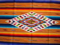 Mexican vintage textiles and sarapes, a lovely Saltillo sarape with a wonderful center diamond of silk, c. 1920's. The predominant color is a lovely golden tan, with very colorful intermittant bands. Photo of center diamond of sarape.