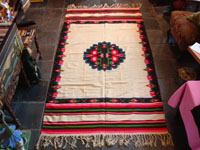 Mexican vintage textiles and sarapes, a lovely weaving from Oaxaca, c. 1940's. The textile is beautifully woven of fine wool. It has a white background with lovely flowers in the border and a beautiful center medallion.