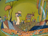Mexican vintage pottery and ceramics, a very fine pottery charger with a rare lime-green background and wonderfully beautiful artwork, Tlaquepaque, Jalisco, c. 1920-30's. The charger features a wonderful scene of rural Mexican life. Closeup photo of the capesino on the front of the Mexican vintage pottery charger.