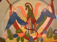 Mexican vintage pottery and ceramics, a magnificent and extremely large charger featuring the Mexican national symbol, an eagle with snake in mouth and two Mexican flags, Tonala or Tlaquepaque, Jalisco, c. 1920-30's. Closeup photo of the eagle on the front of the charger.