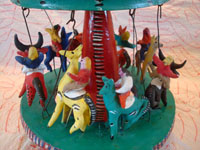 Mexican vintage folk art, and Mexican vintage pottery and ceramics, a beautiful and very whimsical, pottery merry-go-round with eight happy riders mounted on bulls, a giraffe, and horses, attributed to the great Candelario Medrano, Santa Cruz de las Huertas, Jalisco, c. 1950-60's. Closeup photo of the riders.