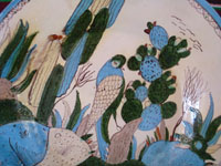 Mexican vintage pottery and ceramics, a wonderful pottery charger decorated with cacti and wonderful birds eating the tunas from a cactus, Tonala or Tlaquepaque, Jalisco, c. 1930's. Closeup photo of the bird eating tunas of the cactus.